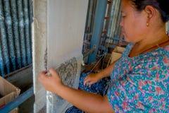 博克拉,尼泊尔- 2017年10月06日:关闭工作在织布机制造业羊毛披肩衣物的未认出的妇女  免版税库存图片