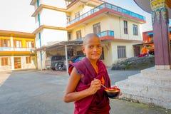 博克拉,尼泊尔- 2017年10月06日:关闭拿着在他的手上一个金属碗用汤的和尚少年在 库存图片