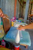 博克拉,尼泊尔- 2017年10月06日:关闭转动羊毛的人对制造的whool披肩衣物在尼泊尔 库存照片