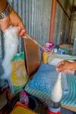 博克拉,尼泊尔- 2017年10月06日:关闭转动羊毛的人对制造的whool披肩衣物在尼泊尔 库存图片