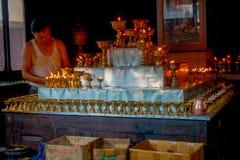 博克拉,尼泊尔- 2017年10月06日:在acomodating在一座金属金字塔的修道院里面的Unidentifed人一些candels 免版税库存照片