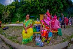博克拉,尼泊尔- 2017年11月04日:坐在一个公共场所的未认出的小组妇女等待和佩带典型 库存图片