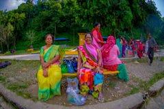 博克拉,尼泊尔- 2017年11月04日:坐在一个公共场所的未认出的小组妇女等待和佩带典型 免版税库存图片