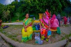 博克拉,尼泊尔- 2017年11月04日:坐在一个公共场所的未认出的小组妇女等待和佩带典型 库存照片