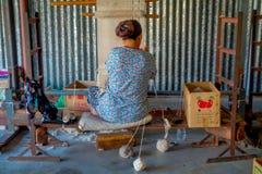 博克拉,尼泊尔- 2017年10月06日:工作在织布机制造业羊毛披肩衣物的未认出的妇女在尼泊尔 免版税库存图片