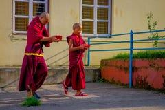 博克拉,尼泊尔- 2017年10月06日:拿着在他们的手上一个红色碗和走在的未认出的和尚teenarger 免版税库存图片