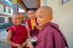 博克拉,尼泊尔- 2017年10月06日:握在他的手的未认出的和尚少年一个金属碗用汤和 库存图片