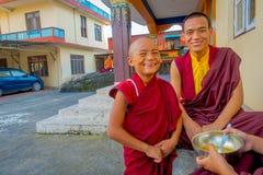博克拉,尼泊尔- 2017年10月06日:握在他的手的未认出的和尚少年一个金属碗用汤和 免版税库存图片