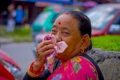 博克拉,尼泊尔- 2017年11月04日:摆在为照相机的老妇人画象在博克拉,尼泊尔,在一个被弄脏的城市 库存照片