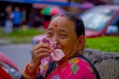 博克拉,尼泊尔- 2017年11月04日:摆在为照相机的老妇人画象在博克拉,尼泊尔,在一个被弄脏的城市 图库摄影