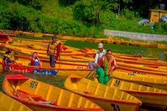 博克拉,尼泊尔- 2017年11月04日:用浆划小船的家庭在有在Begnas湖的湖在博克拉,尼泊尔 免版税库存图片