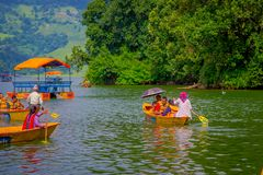 博克拉,尼泊尔- 2017年11月04日:用浆划小船的未认出的人民在有在Begnas湖的湖在博克拉 免版税库存照片