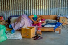 博克拉,尼泊尔- 2017年10月06日:睡觉在一把坚硬干草以后的未认出的老妇人运作在织布机制造业羊毛 免版税库存照片