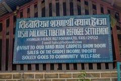 博克拉,尼泊尔- 2017年10月06日:被写在一金属老和生锈的西藏难民settlemente的情报标志 免版税图库摄影