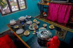 博克拉,尼泊尔- 2017年10月06日:被分类的尼泊尔早餐在桌,牛奶,瓶子coffe,盘,板材上服务里面  库存照片
