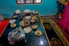 博克拉,尼泊尔- 2017年10月06日:被分类的尼泊尔早餐在桌,牛奶,瓶子coffe,盘,板材上服务里面  免版税库存照片