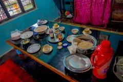 博克拉,尼泊尔- 2017年10月06日:被分类的尼泊尔早餐在桌,牛奶,瓶子coffe,盘,板材上服务里面  免版税图库摄影