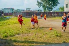 博克拉,尼泊尔- 2017年10月06日:踢足球的未认出的和尚少年在萨迦派Tangyud修道院  库存图片