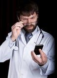 博士 一件白色医疗长袍的有胡子的人,在他的脖子的听诊器,情感地谈话在电话 图库摄影