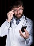 博士 一件白色医疗长袍的有胡子的人,在他的脖子的听诊器,情感地谈话在电话 库存图片