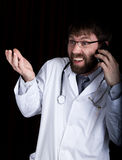 博士 有胡子的manin一件白色医疗长袍,在他的脖子的听诊器,情感地谈话在电话 免版税库存图片