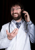 博士 有胡子的manin一件白色医疗长袍,在他的脖子的听诊器,情感地谈话在电话 免版税库存照片