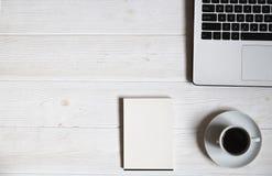 博客作者/商人/女实业家,它与膝上型计算机,黑屏智能手机,咖啡的专家` s白色木办公室空间桌 库存图片