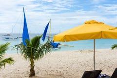 博拉凯海滩、小棕榈树和一把黄色遮阳伞 库存照片