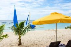 博拉凯海滩、小棕榈树和一把黄色遮阳伞 免版税库存照片