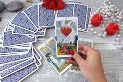 占卜用的纸牌、蜡烛和辅助部件在一张木桌上 免版税库存图片
