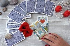 占卜用的纸牌、蜡烛和辅助部件在一张木桌上 免版税库存照片