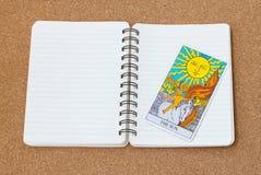 占卜用的纸牌与笔记本和空间的太阳 图库摄影