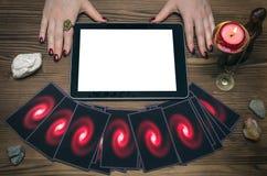 占卜用的纸牌和片剂计算机垫有黑屏的有拷贝空间的 算命者 网上占卜 免版税库存照片