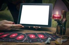 占卜用的纸牌和片剂计算机垫有黑屏的有拷贝空间的 算命者 网上占卜 免版税库存图片