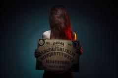 占卜的OUIJA委员会 拿着OUIJA委员会的女孩 有长的红色头发的万圣夜妇女 神秘的占卜交谈 免版税库存照片