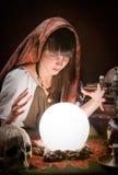 占卜者和一个水晶球 免版税库存图片