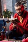 占卜者读书坐在与蜡烛的桌上的占星术书 免版税库存图片