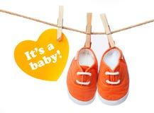 贺卡'它是婴孩'婴孩的运动鞋 库存图片