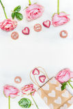 贺卡与桃红色玫瑰、巧克力心脏、纸购物袋和文本您的和充满爱在白色木背景, 库存照片