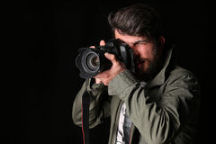 卡其色的夹克的摄影师拍照片 关闭 黑色背景 库存图片