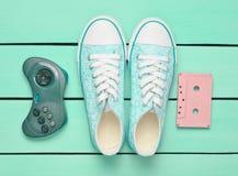 卡型盒式录音机, gamepad,在绿松石柔和的淡色彩背景的运动鞋鞋子 免版税库存照片