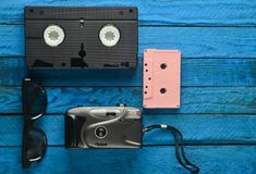 卡型盒式录音机, vhs, 3d玻璃,行家在黄色木背景的影片照相机 从80s的减速火箭的设备 顶视图 免版税库存图片