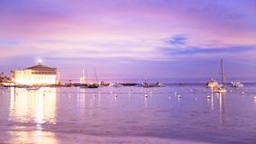卡塔利娜海岛垂距的赌博娱乐场与在海湾的船在与紫色天空的日落 免版税图库摄影
