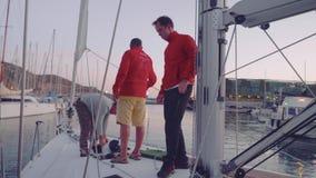 卡塔赫钠,西班牙-大约2017年11月:驾游艇者放停泊和防御者入衣物柜在unmooring游艇以后 股票录像
