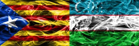 卡塔龙尼亚对乌兹别克斯坦拷贝肩并肩被安置的烟旗子 加泰罗尼亚语和乌兹别克斯坦浓厚色的柔滑的烟旗子复制 免版税库存照片