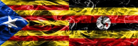 卡塔龙尼亚对乌干达拷贝肩并肩被安置的烟旗子 加泰罗尼亚语和乌干达的浓厚色的柔滑的烟旗子复制 库存照片