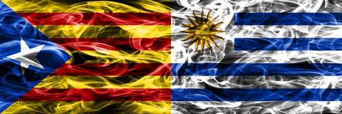 卡塔龙尼亚对乌拉圭拷贝肩并肩被安置的烟旗子 加泰罗尼亚语和乌拉圭的浓厚色的柔滑的烟旗子复制 免版税库存照片