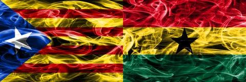 卡塔龙尼亚对加纳拷贝肩并肩被安置的烟旗子 加泰罗尼亚语和加纳的浓厚色的柔滑的烟旗子复制 库存图片