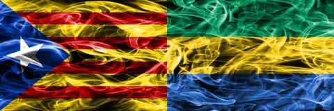 卡塔龙尼亚对加蓬拷贝肩并肩被安置的烟旗子 加泰罗尼亚语和加蓬的浓厚色的柔滑的烟旗子复制 库存图片