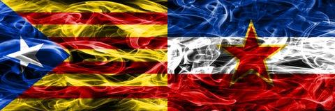 卡塔龙尼亚对南斯拉夫拷贝肩并肩被安置的烟旗子 加泰罗尼亚语和南斯拉夫的浓厚色的柔滑的烟旗子复制 免版税库存照片
